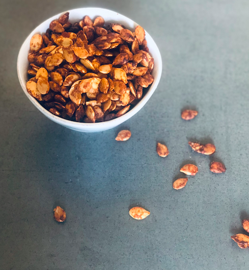 Roasted pumpkin seeds are in a white bowl, on a gray background, with some seeds scattered to the bottom right of the bowl.